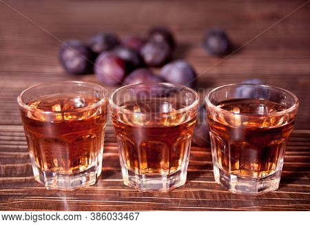 Plum Vodka Or Brandy With Fresh Plums On The Wooden Table.