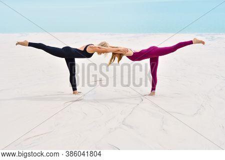 Two Beautiful Young Women Perform Pose Yoga Virabhadrasana On The Beach