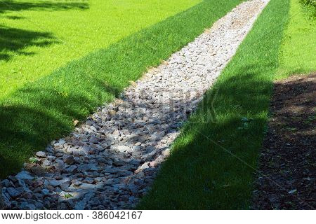 Selective Focus, Drainage, A Drainage System In A Park Area, A Waterway Overgrown With Lawn And Pave