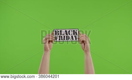 Black Friday Advertisement Inscription On Paper Sheet In Womans Hands On Green Screen. Holiday Disco