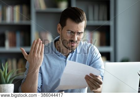 Unhappy Young Man Read Unpleasant Message In Correspondence
