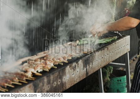 Hand Of Young Man Grilling Some Meat And Vegetables On Long Rectangular Barbecue With Smoke On The S