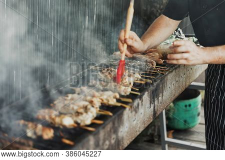 Blurred Hands Of Man Lubricates The Meat With A Sauce Brush On Long Rectangular Barbecue With Smoke