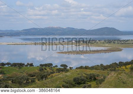 Lake Reservoir Water Reflection Of Alqueva Dam Landscape And Monsaraz On The Foreground In Alentejo,