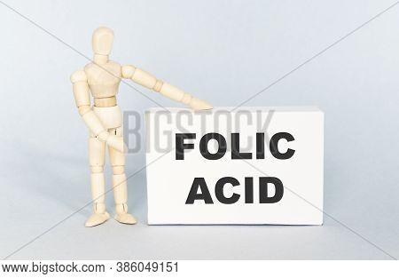 Folic Acid Written On The Wooden Man Figurine Card.