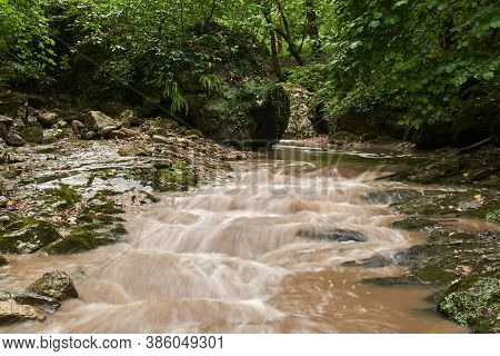 Muddy Stream After Rain In A Subtropical Forest, The Water Is Blurred In Motion