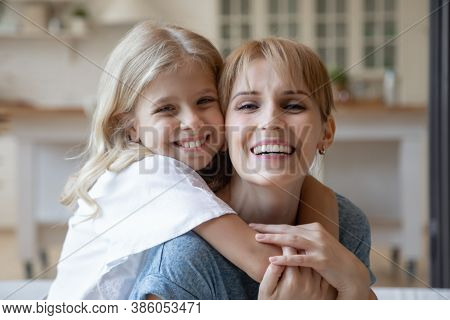 Joyful Mother Cuddling With Her Child At Home And Smiling