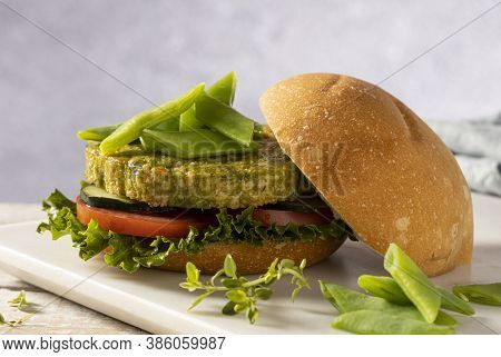 Vegan Hamburger Made With Green Beans And Chickpeas, Served With Tomato, Cucumber And Lettuce.