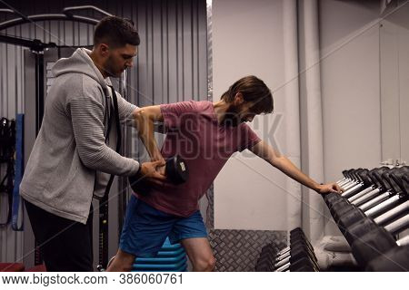 Beginner Man Doing Chest And Shoulder Dumbbell Press With Personal Coach , Trainer Demonstrates The