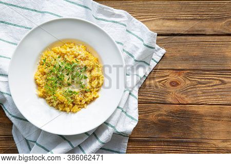 Fall (autumn) Risotto On Rustic Wooden Background, Top View. Pumpkin With Parmesan And Marjoram.