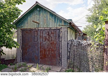 Rural Old Garage With Wooden Loft And Iron Red Rusty Gates On The Street