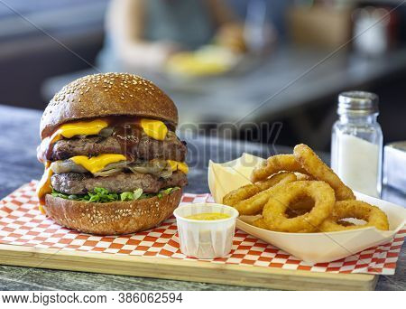 A Double Cheeseburger With Dripping Melted Cheese Served With Onion Rings At A Fast Food Restaurant.