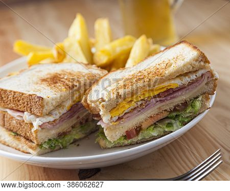 Homemade Club Sandwich With Ham, Cheese, Egg, Lettuce And Tomato.