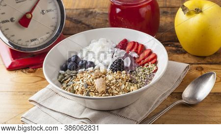 Healthy Breakfast Bowl With Oats, Sunflower Seeds, Coconut, Blueberries And Strawberries.