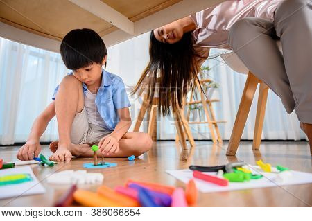 Asian Mother Work Home Together With Son. Mom Online Working And Kid Play Dough Under Table. Woman L