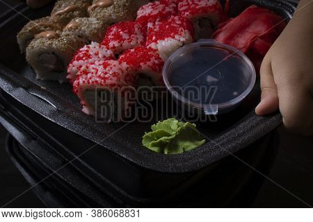 Hands Hold Set Of Red And Yellow Sushi Rolls. Dark Mood Photo