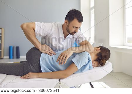 Man Doctor Chiropractor Or Osteopath Fixing Lying Womans Back In Manual Therapy Clinic