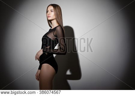 Profile Portrait Of A Attractive Slim Young Woman With Long Hair And Make-up, Wear In Bodysuit, Over