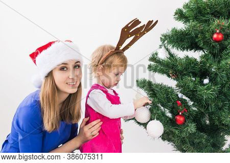 Mother And Daughter Decorating Christmas Tree And Having Fun. Holidays And Celebration Concept.