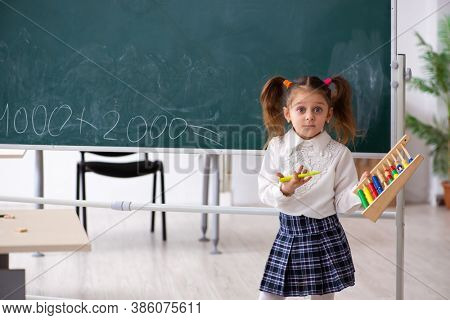 Small girl in front of blackboard in the classroom