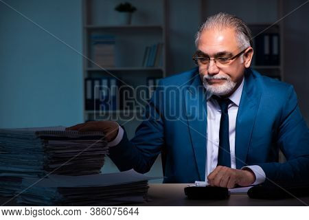 Old male employee working late in the office