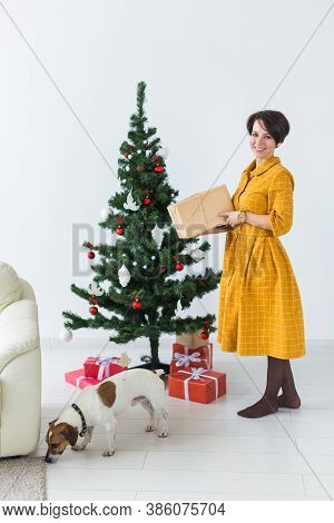 Happy Young Woman With Lovely Dog Opening Present Box Under Christmas Tree. Holidays Concept.
