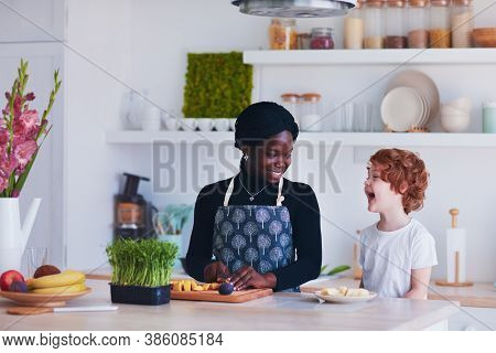 Cheerful Multiracial Family, Mother And Son Having Fun On The Kitchen