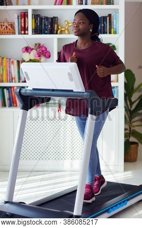 Young Black Woman Is Exercising On A Treadmill At Home, Healthy Lifestyle