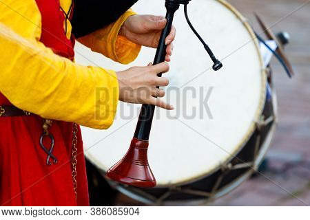 Woman In Medieval Costume Plays The Bagpipes. Close-up
