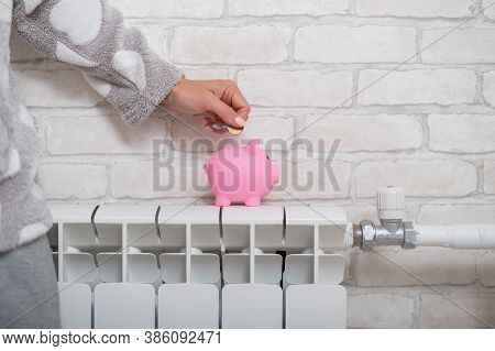 Female Hand Putting Coin Into Piggy Bank Which Standing On Heating Radiator With Temperature Regulat