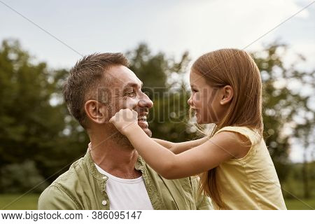 Fathers Day. Cute Little Girl Playing With Her Daddy While Visiting Park On A Summer Day, Touching H