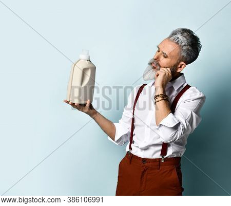 Bearded Old Man Shows An Empty Mockup Of A Plastic Paper Container With An Effective Detergent And L