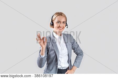 Happy Call Centre Operator With Headset Showing Okay Gesture On Light Background, Panorama. Portrait