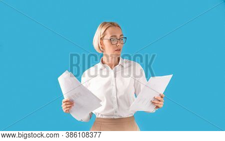 Portrait Of Serious Businesswoman In Formal Clothes And Eyeglasses Holding Documents Over Blue Studi