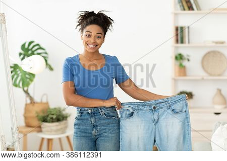 Weight Loss. Happy Slim Black Woman Showing Old Oversize Jeans After Successful Diet Slimming Standi