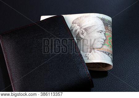 Seventy Five Of Banknote Currency Myanmar Kyats With Black Wallet On The Black Floor. It Is The Retr