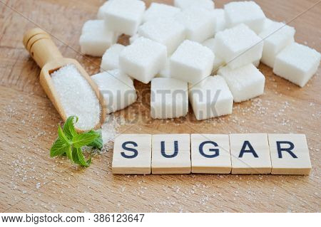 Refined Sugar, Wooden Spoon With Loose Sugar And Fresh Mint Leaves On Wooden Background. Word Sugar