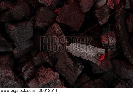 Smoldering Charcoal With Ash Background. Incandescent Red Embers Texture. Dark Background.