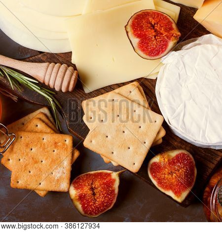 Cheese Board With Brie, Maasdam, Gouda And Goat Cheese, Figs, Honey And Jam. Appetizer Assortment On