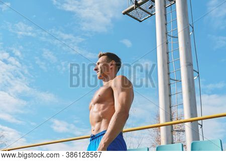 Middle Aged Toned Man Stands Shirtless Under Sunlight And Getting Rest After Workout. Outdoors Sport
