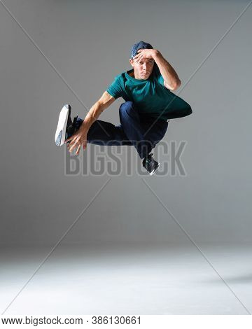 Cool Young Guy Breakdancer Jumps In Studio Isolated On Gray Background. Dance School Poster. Break D