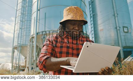 African Farmer Using Laptop In Front Of The Silo Storage System. High Quality Photo