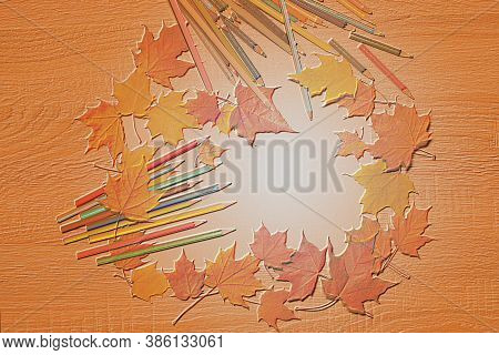 Illustration With Pencils And Maple Leaves On A Wooden Table With An Embossing Effect On An Orange O