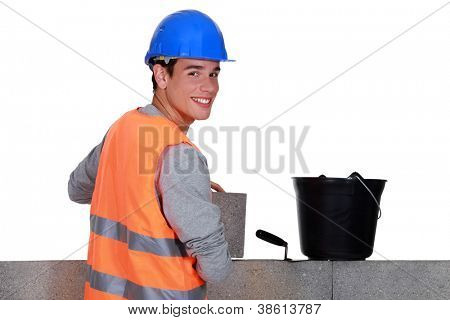 Young mason happily working away