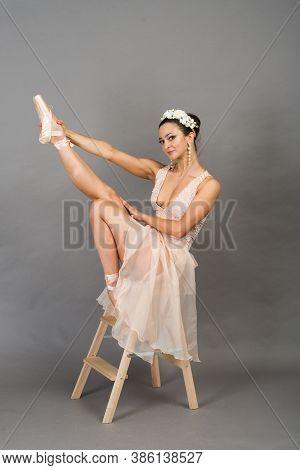 Beautiful Ballet Dancer Posing On Pointes On Light Grey Studio Background