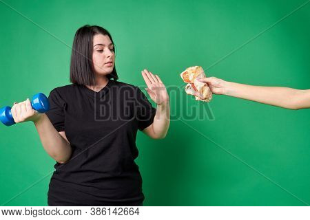 Fat Young Woman Refuses Junk Food. Hand Is Offering Unhealthy Food. American Thick Lady With Blue Du