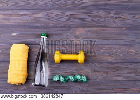 Topview Of Items For Sport. Yellow Towel, Measure Tape And Glass Bottle With With Dumbbell On The Wo
