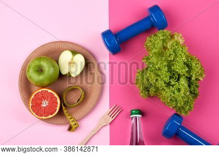 Healthy Food And Fitness Concept. Green Lettuce, Apple And Graiphrute On The Plate. Blue Dumbbells O
