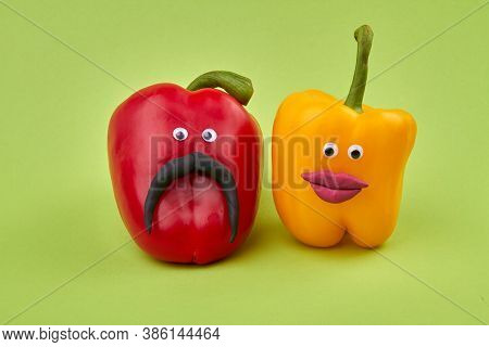 Couple Of Bell Peppers. Red Husband Pepper And Yellow Wife Pepper On Green Background.
