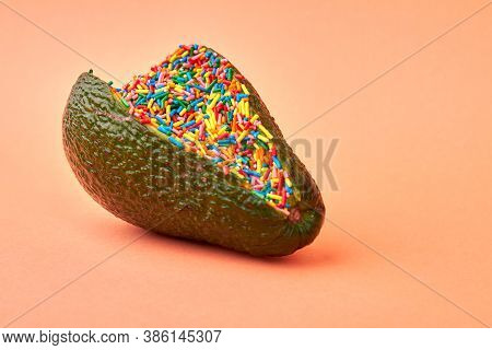 Avocado Filling With Sweet Candy Sprinklers. Close Up Green Avocado Full Of Multicolored Sprinklers